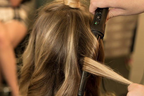 Woman Getting Her Hair Curled With Curling Iron
